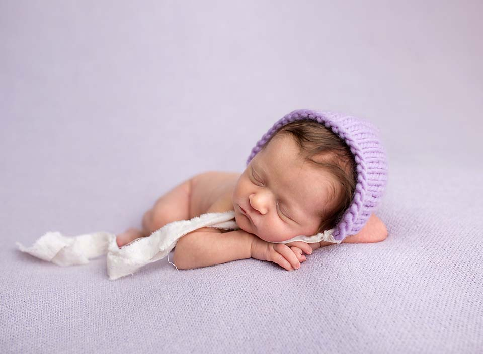 Sleeping newborn on purple blanket with bonnet, professional newborn photography serving Uxbridge